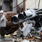 A construction worker controls the traffic at a devastated area in Kesennuma, northern Japan, while traffic lights destroyed by the tsunami lie behind him. (AP Photo/Shizuo Kambayashi)