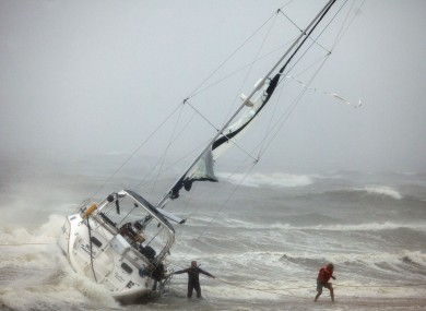 One of two people rescued from a sailboat, right, uses a line to make their way onto the beach on Willoughby Spit in Norfolk, Virgina yesterday.
