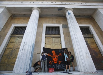 Protesters place a placard on the door of Greece's Central Bank, during an anti-austerity protest in Athens