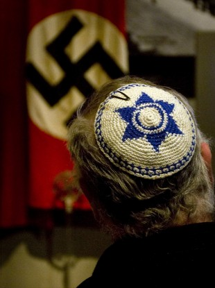 A Jewish man looks at exhibit showing the Nazi flag, during a visit at Yad Vashem Holocaust Memorial in Jerusalem Sunday, April 11, 2010