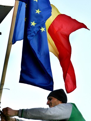 A Romanian man hoists EU and Romanian flags in Bucharest after Romania's entry to the EU in 2007.