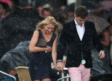 Racegoers dash for cover on Ladies Day at York's Ebor Festival.