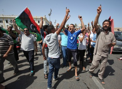 Libyans hold up their ink marked fingers after voting in last month's elections