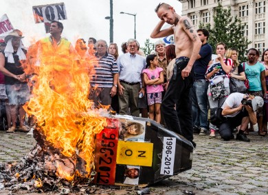 Demonstrators gather around a burning mock coffin with the pictures Marc Dutroux and M