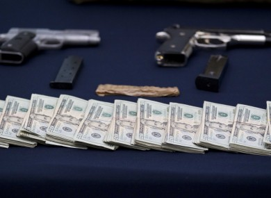 Mexican police display guns and cash seized from the Zetas drug cartel in previous raids.