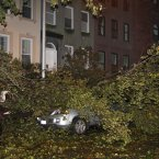 A fallen tree branch sits on a car blocking East 74th St. between Lexington Avenue and Third Avenue on Manhattan's Upper West Side on Monday. Sandy made landfall Monday night, hurling a surge of seawater on New York City with wind and rain that sent water sloshing into Manhattan from three sides but began dying down within hours. (AP Photo/Willie Regan)