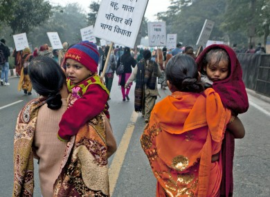 Indian women carry their children as they march during a protest to mourn the death of a gang rape victim in New Delhi.
