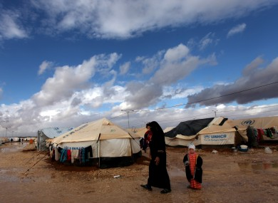 A Syrian refugee woman walks with her two kids at Zaatari Syrian refugee camp, near the Syrian border in Mafraq, Jordan.