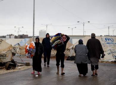 Syrian refugees carry their belongings at Zaatari refugee camp, near the Syrian border in Mafraq, Jordan.