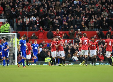 Manchester United's Ryan Giggs celebrates scoring his team's first goal of the game with teammates as Everton players look on dejected.