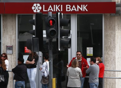People wait and use the ATM of a closed branch of Laiki Bank in capital Nicosia