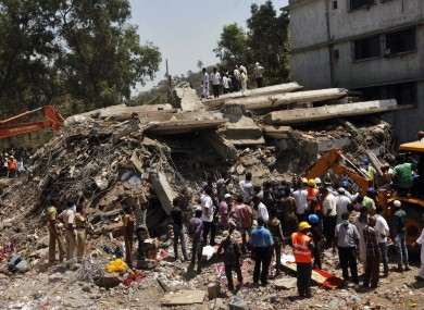 People gather around a heap of debris at the site of a building collapsed as a rescue operation continues.