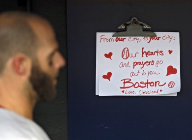 Boston Red Sox's Dustin Pedroia walks past a condolence sign in the dugout .