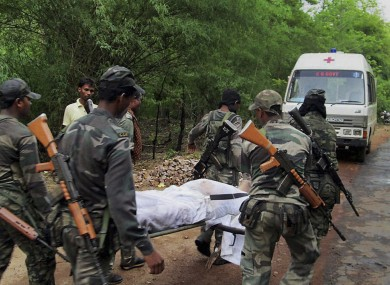 Indian security personnel carry the body of one of the victims of the Maoist attack in a densely forested area in Bastar.