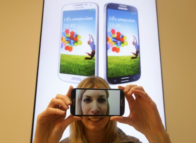 A woman holding the Samsung Galaxy S4 smartphone which went on sale at the Samsung Experience Store in east London