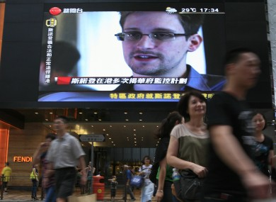 A TV screen shows a Chinese news report of Edward Snowden.