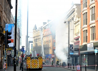 Firefighters at the scene of a fire at Paul's Hair World in Oldham Street, Manchester, where firefighter Stephen Hunt, 38, was killed whilst tackling the blaze at the city centre shop.