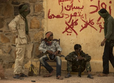 Rebels from the National Movement for the Liberation of the Azawad (NMLA) stand guard outside the former governor's office, in Kidal, Mali.