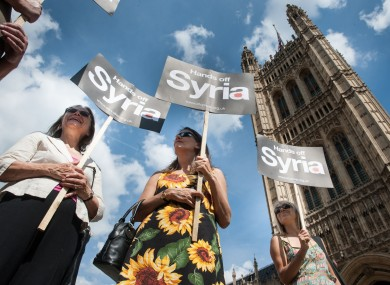 Protestors demonstrating against military action in Syria stand outside the Houses of Parliament in Westminster, London.