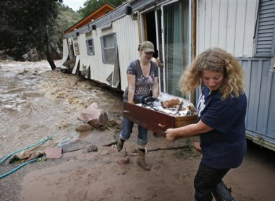 As water rushes through her destroyed home as resident Holly Robb, left, and her neighbor Pam Bowers salvage belongings