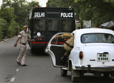 A police car escorts the van carrying four men convicted in the fatal gang rape of a young woman on a moving New Delhi bus.